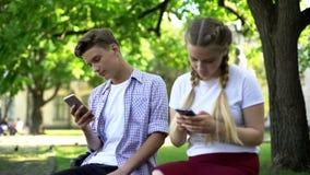 Adolescents indifférents mettant en rouleau des smartphones en parc, problème de dépendance d'instrument images libres de droits