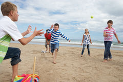 Adolescents jouant au base-ball sur la plage Images stock