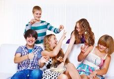 Adolescents jouant avec le maïs éclaté Images stock