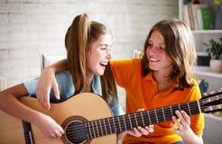 Adolescents jouant la guitare images stock