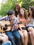 Adolescents jouant la guitare et le chant Image stock