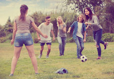 Adolescents jouant le football en parc Photographie stock