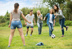 Adolescents jouant le football en parc Image libre de droits