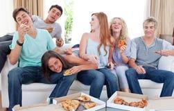Adolescents mangeant de la pizza à la maison Photo stock