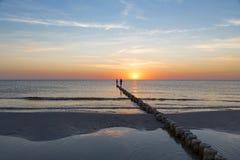 Adolescents marchant sur une aine au coucher du soleil Images stock