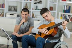 2 adolescents masculins jouant la guitare acoustique et le chant Image stock