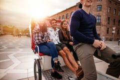 Adolescents montant sur le tricycle et ayant l'amusement Image libre de droits