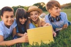Adolescents multi-ethniques avec le comprimé numérique Photographie stock
