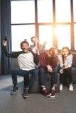 Adolescents multiculturels heureux jouant des jeux vidéo avec des manettes à la maison Photographie stock libre de droits