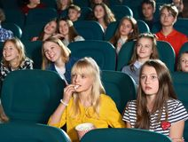 Adolescents observant le film intéressant et souriant dans le cinéma Photographie stock