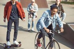 Adolescents passant le temps en parc de planche à roulettes, adolescents ayant le concept d'amusement Photos stock