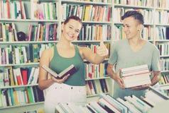 Adolescents positifs achetant de nouveaux livres et montrant des pouces  Photo libre de droits