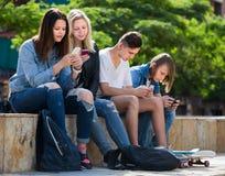 Adolescents positifs jouant avec des téléphones portables Photo stock