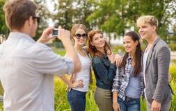 Adolescents prenant l'appareil photo numérique de photo dehors Images libres de droits