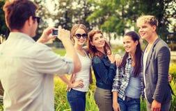 Adolescents prenant la photo avec l'appareil photo numérique dehors Photographie stock libre de droits