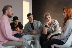 Adolescents rebelles écoutant une fille de gingembre au cours d'une réunion photo libre de droits