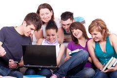 Adolescents regardant l'ordinateur portatif Photos stock