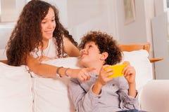 Adolescents riants causant utilisant le téléphone portable Photographie stock libre de droits
