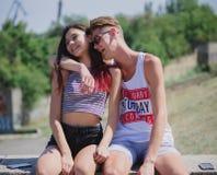 Adolescents riants détendant sur un fond naturel Couples romantiques étreignant en parc de ville Jeune concept de relations Photographie stock