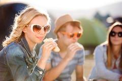 Adolescents s'asseyant au sol devant des tentes et la consommation Image stock