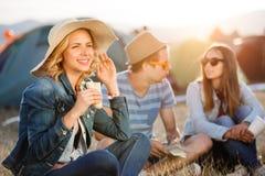 Adolescents s'asseyant au sol devant des tentes, se reposant Image stock