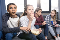 Adolescents s'asseyant sur le sofa et mangeant du maïs éclaté de la cuvette à l'intérieur Photo libre de droits