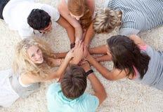 Adolescents se trouvant sur l'étage avec des mains ensemble Photographie stock