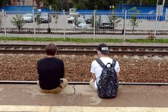 Adolescents sit on the edge of the railway platform. KOROLEV, RUSSIA - AUGUST 3, 2016: Adolescents sit on the edge of the railway platform stock photo