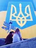 Adolescents situant sur le fond ukrainien de drapeau Photos stock