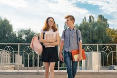 Adolescents students with backpacks, textbooks, go to school. Outdoor portrait of teenage boy and girl 14, 15 years old.  stock image