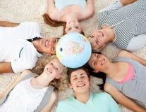 Adolescents sur l'étage avec un globe au centre Images libres de droits
