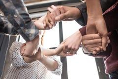Adolescents tenant des mains ensemble à l'intérieur, adolescents ayant le concept d'amusement Photos stock