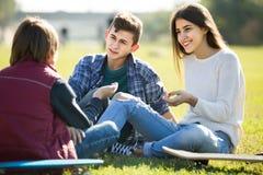 Adolescents traînant dehors et discutant quelque chose Image libre de droits