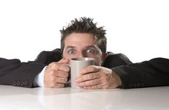 Adonnez-vous à l'homme d'affaires dans le costume et attachez tenir la tasse de café comme fou dans la dépendance de caféine Photographie stock libre de droits