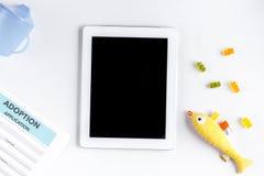 Adopción de concepto con la tableta en maqueta de la opinión de sobremesa Imagenes de archivo