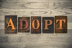 Adopt Wooden Letterpress Theme. The word ADOPT theme written in vintage, ink stained, wooden letterpress type on a wood grained background. theme written in stock image