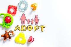 Adopte la palabra, la silueta de papel de la familia y los juguetes en el copyspace blanco de la opinión superior del fondo Foto de archivo