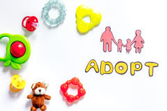 Adopte la palabra, la silueta de papel de la familia y los juguetes en el copyspace blanco de la opinión superior del fondo Fotografía de archivo libre de regalías
