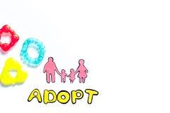 Adopte la palabra, la silueta de papel de la familia y los juguetes en el copyspace blanco de la opinión superior del fondo Imagen de archivo