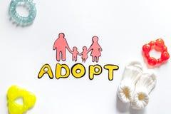 Adopte la palabra, la silueta de papel de la familia y los juguetes en el copyspace blanco de la opinión superior del fondo Fotos de archivo