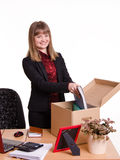 Adopted in office girl puts her things out of the box Royalty Free Stock Photos