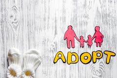 Adoptez le mot et la silhouette de papier de la famille sur le copyspace en bois léger de vue supérieure de fond de table Image stock