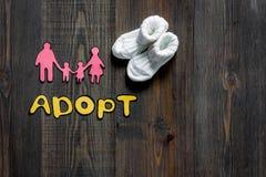 Adoptez le mot, la silhouette de papier de la famille et les butins sur le copyspace en bois foncé de vue supérieure de fond de t Photographie stock