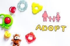 Adoptez le mot, la silhouette de papier de la famille et les jouets sur le copyspace blanc de vue supérieure de fond Photographie stock libre de droits