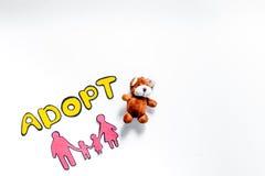 Adoptez le mot, la silhouette de papier de la famille et les jouets sur le copyspace blanc de vue supérieure de fond Photographie stock