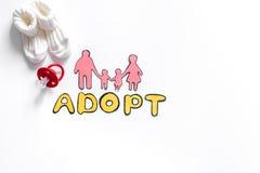 Adoptez le mot, la silhouette de papier de la famille et les jouets sur le copyspace blanc de vue supérieure de fond Images stock
