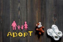 Adoptez le mot, la silhouette de papier de la famille et les jouets sur le copyspace en bois foncé de vue supérieure de fond de t Images stock