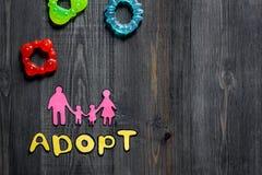Adoptez le mot, la silhouette de papier de la famille et les jouets sur le copyspace en bois foncé de vue supérieure de fond de t Image libre de droits