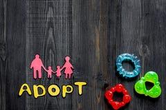 Adoptez le mot, la silhouette de papier de la famille et les jouets sur le copyspace en bois foncé de vue supérieure de fond de t Photographie stock