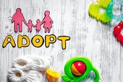 Adoptez le mot, la silhouette de papier de la famille et les jouets sur le copyspace en bois léger de vue supérieure de fond de t Image libre de droits